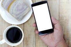 Smartphone van de handholding met ontbijt op de houten lijst wordt geplaatst die stock foto