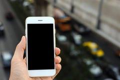 Smartphone van de handholding met opstoppingachtergrond Stock Fotografie