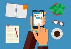 Smartphone van de handholding met tekstberichten op het scherm Op de Desktop, de Blocnote, de pen, de bloem, de koffiekop en de d stock illustratie