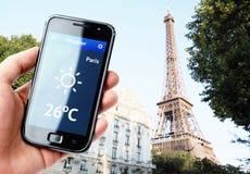 Smartphone van de handholding met weer in Parijs stock afbeelding