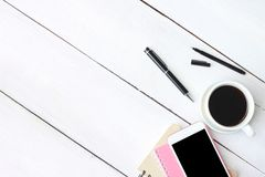 Smartphone van de koffiekop en pen, notitieboekje op wit houten bureau en stock fotografie
