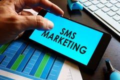 Smartphone van de mensenholding met sms marketing royalty-vrije stock afbeeldingen