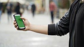 Smartphone van de mensenholding in openbaar straatpark wat betreft het groene scherm met chromasleutel stock videobeelden