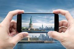 Smartphone van de reizigersholding om een foto van het Standbeeld van Vrijheid te nemen stock fotografie