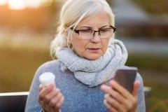 Smartphone van de vrouwenholding en pillenfles royalty-vrije stock afbeelding