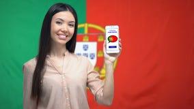 Smartphone van de vrouwenholding met taalstudie app, Portugese vlag over achtergrond stock video