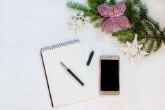 Smartphone van het fotovliegtuig of mobiele telefoon, een notitieboekje voor nota's, pennen en verfraaide boomtak op een witte ho Stock Afbeeldingen