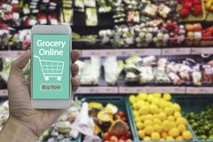 Smartphone van het handgebruik met online kruidenierswinkel Stock Foto