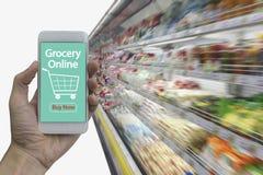 Smartphone van het handgebruik met online kruidenierswinkel Stock Afbeelding
