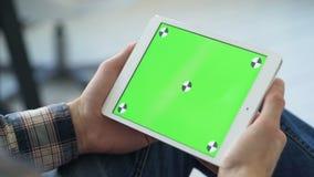 Smartphone van het jonge mensengebruik met greenscreen voor mededeling stock video