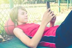Smartphone van het tienergebruik met vrienden voor spelbasketbal openlucht - het gezonde sportieve concept van de tienerslevensst stock foto