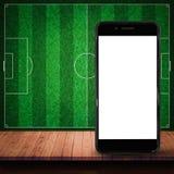 Smartphone vazio na tabela de madeira com o backgrou da parede do campo de futebol Imagens de Stock