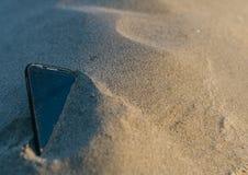 Smartphone verlor im Sand Lizenzfreie Stockfotos
