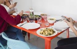 Smartphone, verwendend auf dem Abendtische lizenzfreie stockfotos