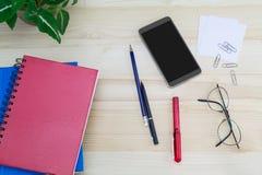 Smartphone, vidrios, cuadernos, pluma, lápiz, clips de papel, verde deja el pote en la tabla de madera del vintage imagenes de archivo