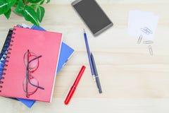 Smartphone, vidrios, cuadernos, pluma, lápiz, clips de papel, verde deja el pote en la tabla de madera del vintage foto de archivo libre de regalías