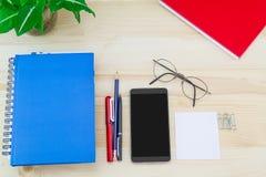 Smartphone, vidrios, cuadernos, pluma, lápiz, clips de papel, verde deja el pote en la tabla de madera del vintage fotos de archivo libres de regalías