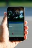 Smartphone w ręka facecie łapie Pokemon na drodze Obraz Stock
