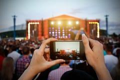 Smartphone w rękach podczas plenerowego rockowego koncerta obrazy royalty free