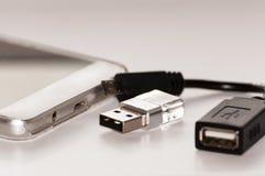 Smartphone waarnaast usb flitsgeheugen en een kabel voor zijn verbinding aan smartphone is Stock Foto