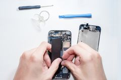 The smartphone was damages and need to repair which tools smartphone that stand on white background. By hands of repairman stock photography