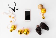 Smartphone-Weihnachtszusammensetzung Kegel und Weihnachtsdekorationen auf weißem Hintergrund Draufsicht der flachen Lage stockfotos