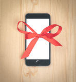 Smartphone with white blank screen tied with a red ribbon on woo Royalty Free Stock Images