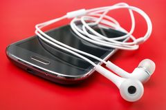 Smartphone with white earphones Stock Photography