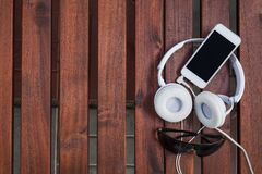 Smartphone white headphone on wood. With sunglasses Stock Images