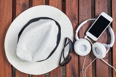 Smartphone white headphone on wood. With sunglasses and hat Royalty Free Stock Photos