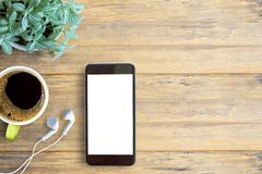 Smartphone white screen, white ear phone and cup of coffee on wo. Oden table background, mockup modern smartphone jet black color.Top view with copy space for Stock Images