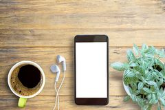 Smartphone white screen, white ear phone and cup of coffee on wo. Oden table background, mockup modern smartphone jet black color.Top view with copy space for Stock Photography