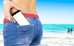 Smartphone with  white screen with empty space for text in a jeans pocket of a young beautiful girl, ocean background.  Royalty Free Stock Image
