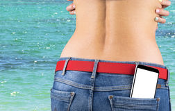 Smartphone with  white screen with empty space for text in a jeans pocket of a young slender girl, ocean background Stock Images