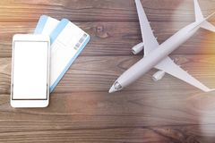 Smartphone with white screen plane tickets. Airplane on wooden background Royalty Free Stock Image