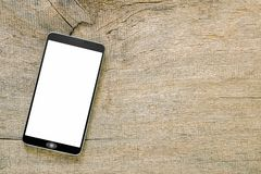 Smartphone on vintage grunge wooden background. Smartphone with white screen on vintage grunge wooden background stock photo