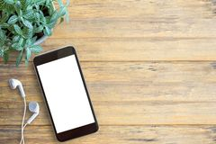 Smartphone white screen, white ear phone and on wooden table bac. Smartphone white screen, white ear phone on wooden table background, mockup modern smartphone Stock Photos
