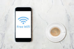 Smartphone with wifi network on screen and coffee cup Royalty Free Stock Photography