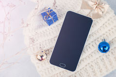 Smartphone and winter hat on white background. Black smart phone with black screen, with copy space and accessories Stock Photos
