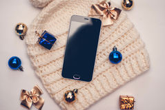 Smartphone and winter hat on white background. Black smart phone with black screen, with copy space and accessories Royalty Free Stock Image