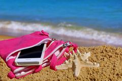 Smartphone in the Woman Purse on the Beach Royalty Free Stock Photo