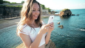 Smartphone woman sms texting using app on smart phone at beach sunset. Mixed stock video footage
