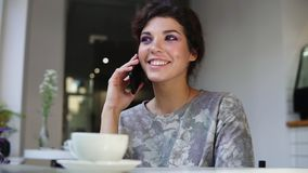 Smartphone woman talking on phone while sitting in cafe with a cup of coffee on the table. She is smiling and laughing. In cafe. Beautiful young female having stock video footage