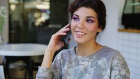 Smartphone woman talking on phone while sitting in cafe. She is smiling. Beautiful young female having casual stock video