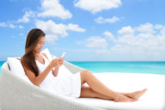 Smartphone woman using phone app on beach bed sofa. Woman using phone app relaxing on sun bed on outdoor terrace. Home living outside patio furniture Asian girl Stock Photo