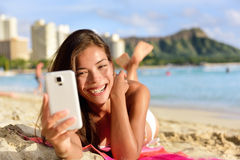 Smartphone woman using smart phone app on beach Stock Images