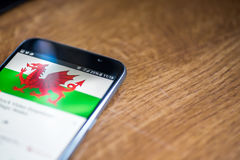 Smartphone on wooden background with 5G network sign 25 per cent charge and Wales flag on the screen Royalty Free Stock Photo