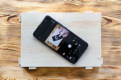 Smartphone on a wooden box with itself image on screen. Remote camera control application concept stock photos