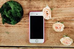 Smartphone on the wooden table of a flower shop next to a plant. Stock Photography