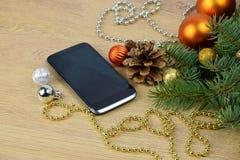 Smartphone y árbol de navidad en fondo de madera greeti del teléfono Fotos de archivo